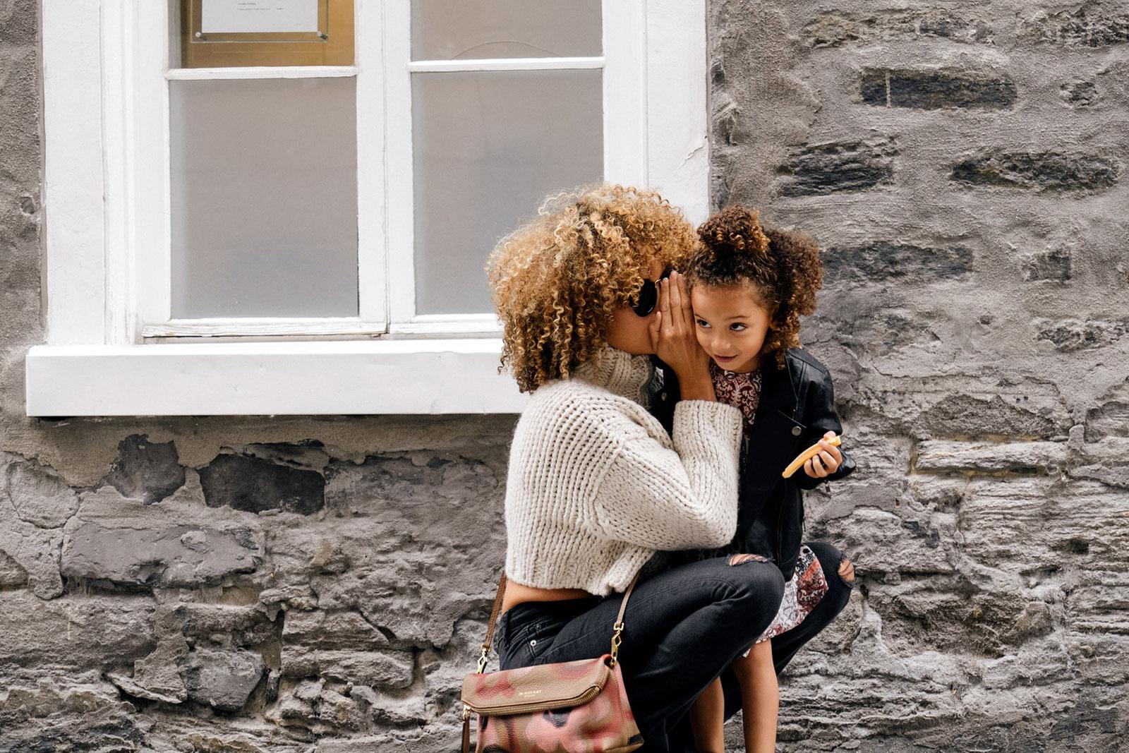 Mulher a segredar ao ouvido de uma criança