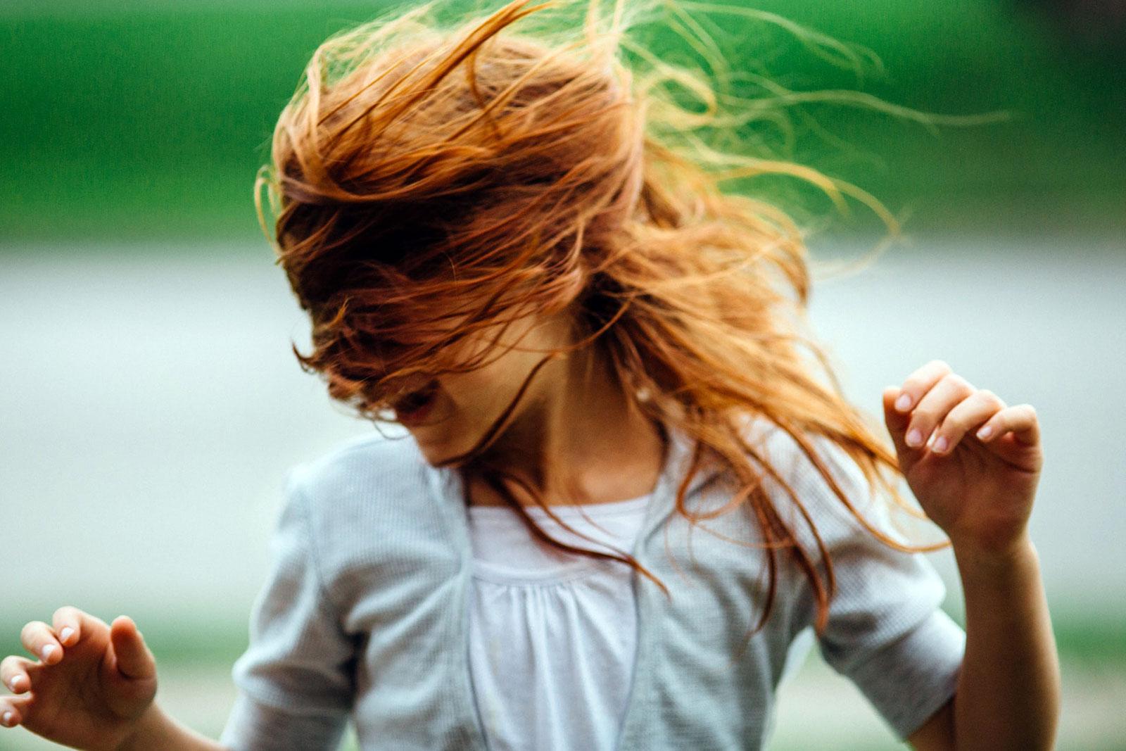 Rapariga a correr com os cabelos a esvoaçar
