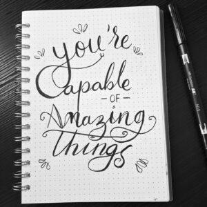 "Caderno com frase ""You'are Capable of Amazing Things"", sobre mesa junto a caneta"