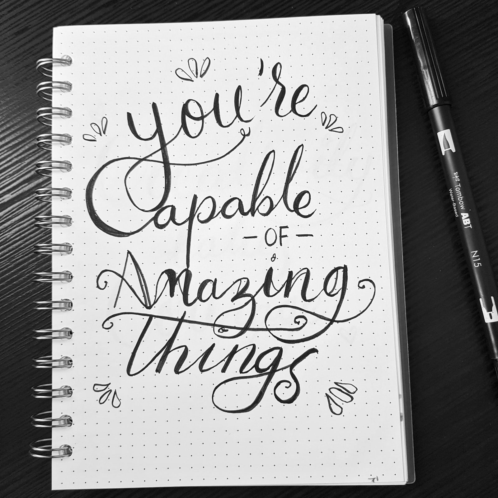 "Caderno com frase ""You'are Capable of Amazing Things"", sobre mesa junto a caneta"