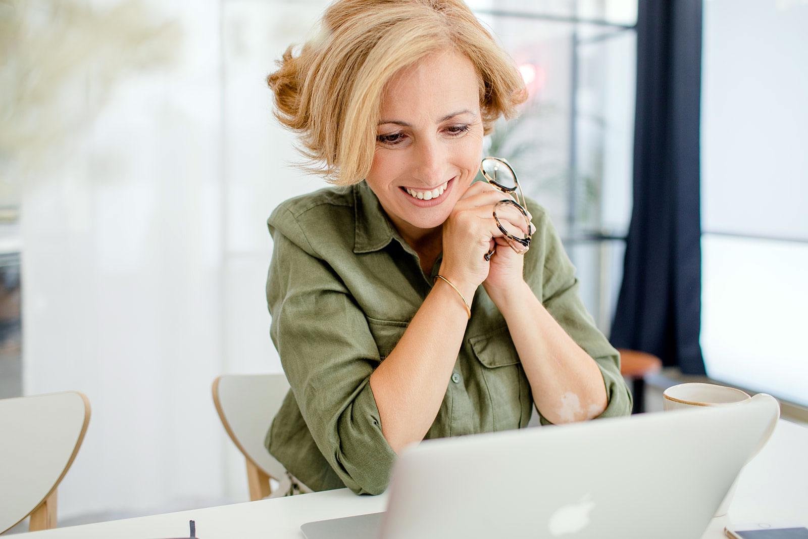Rita Aleluia com óculos nas mãos a olhar para o ecrã de um computador