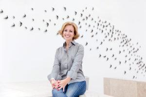 Rita Aleluia sentada junto a parede com andorinhas