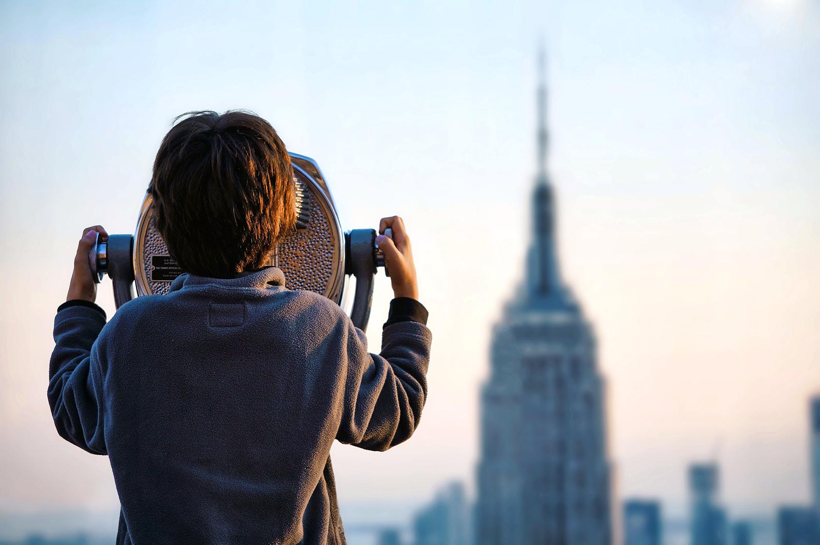 Criança a ver com binóculos o Empire State Building, em Nova Iorque.