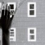 Mão sobre janela com pingos de chuva no exterior