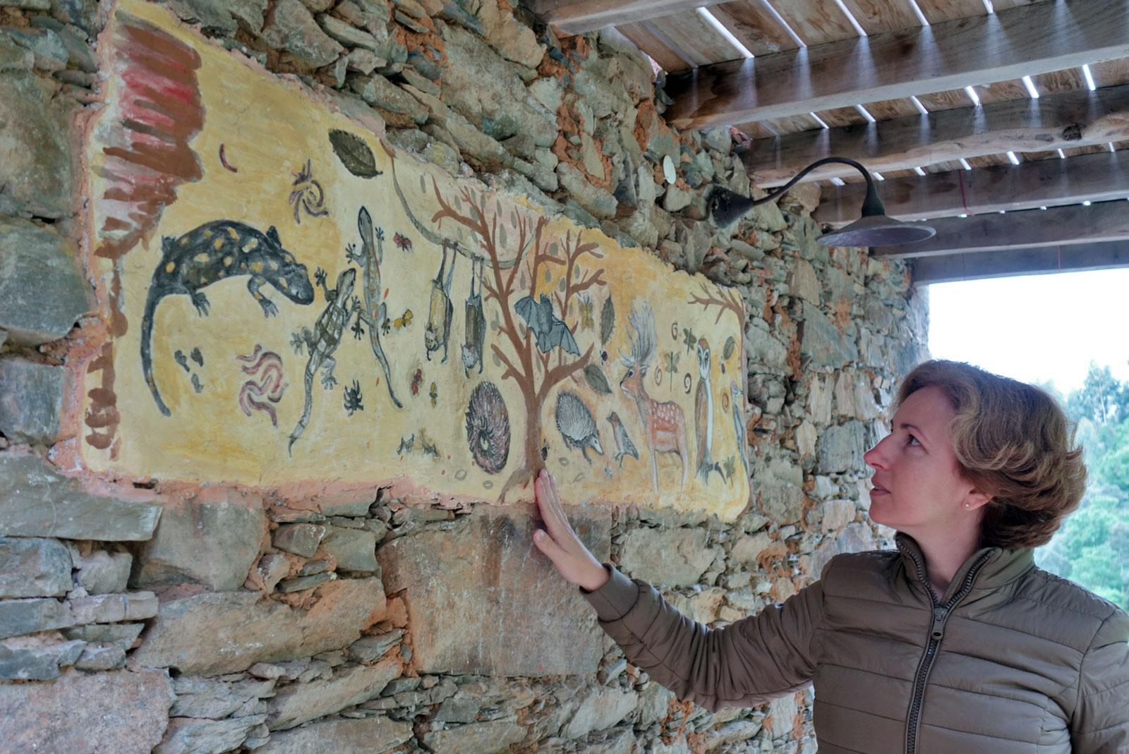 Rita Aleluia junto a parede com pintura de animais, ou uma espécie de arquétipos