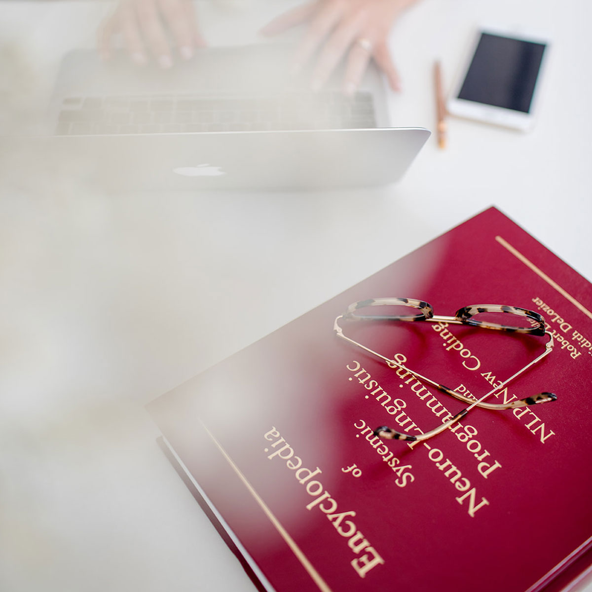 Enciclopédia da PNL, computador, trainer de PNL a trabalhar, óculos, caneta e telemóvel na secretária branca