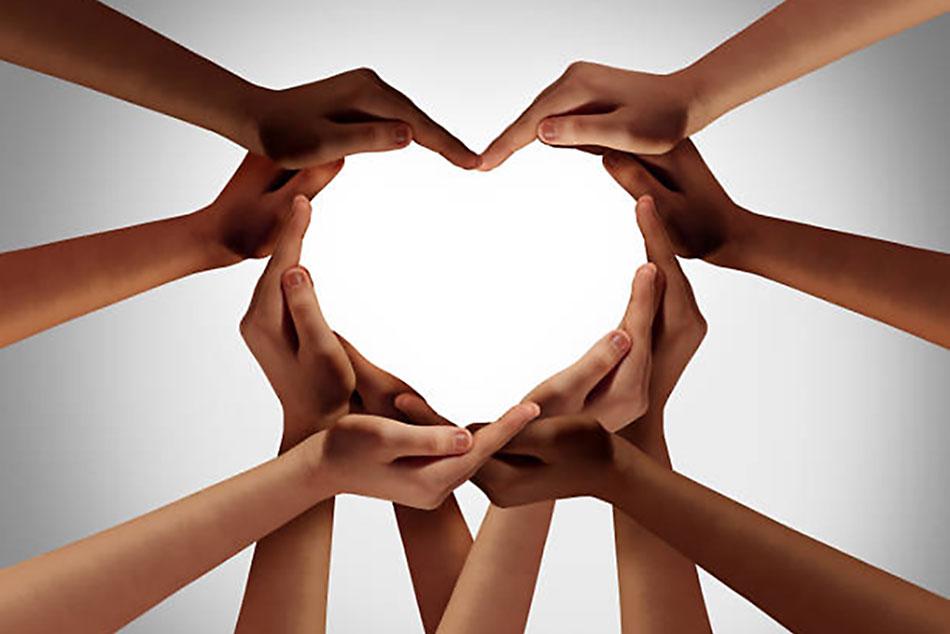 Mão dadas, em forma de coração, representando união e amor, várias etnias, braços de homens e mulheres, em fundo branco.