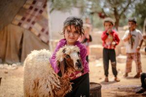 Menina de camisola cor-de-rosa e calças pretas, crianças refugiadas, pobres, a abraçar ovelha e meninos no fundo, em comunidade, com árvores e tenda.